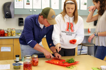 Seniors Luke Zlatunich and Lauren Bell chop up bell peppers and cilantro during the Iron Chef competition in the Sustainable Agriculture class this week.