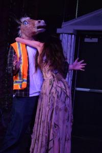 Bottom (left, Riley Christensen) is being hugged by Titania (right, Sydney Pigott)