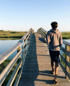 Walking across the bridge at Ridgevale Beach, Jackson Reed looks out at where his camp will soon take place.