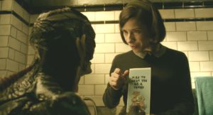Sharing a brief moment of happiness together, Elise (Sally Hawkins) shows the creature (Doug Jones) a card she bought him.