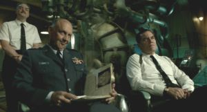 Conducting secret experiments, Colonel Stricken (Michael Shannon) and General Hoyt (Nick Searcy) contemptuously view the injured creature.