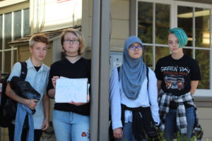 Holding up signs against gun control, a group of students participated in a walkout that ended at Larkspur City Hall.