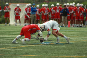 Junior Miles Dean butts heads with an SI player to gain possession of the ball during a face-off.