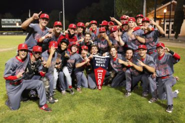 The Redwood varsity baseball team holds up the MCAL banner.