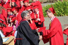 A graduate smiles at Sondheim, accepting his diploma.