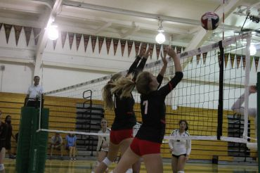 Brooke Leslie and Lucy Walsh, jumping to deflect the ball.