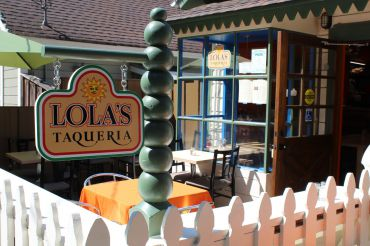 Sidewalk view of Lola's Taqueria includes festive and colorful sign and exterior design