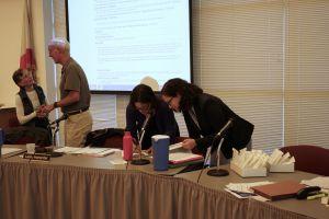 Board president Leslie Lundgren Harlander and new Superintendent Dr. Tara Taupier signing important documents.