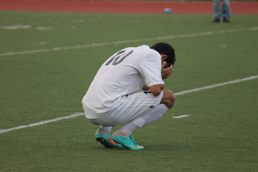 Junior Sasha Boussina holds his head in his hands after Redwood's loss to Marin Catholic on Wednesday