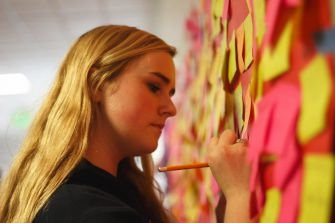SOPHOMORE JULIA HALLORAN contributes a handwritten Post-It to the compliment wall during E.L.E. week.