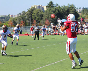 Tight end Enzo Tallerico, junior, turns to catch a pass from quarterback Aaron Dorfler.