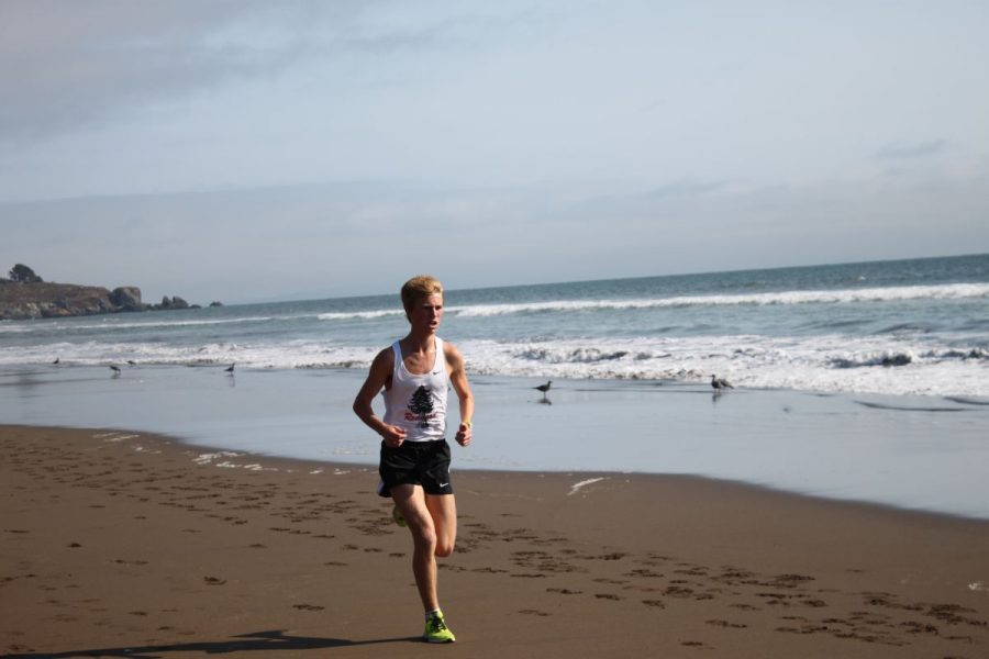 Boys' captain Andy Ehrenberg races along the Stinson shoreline last Tuesday, earning a spot among the top five time scorers of the afternoon.