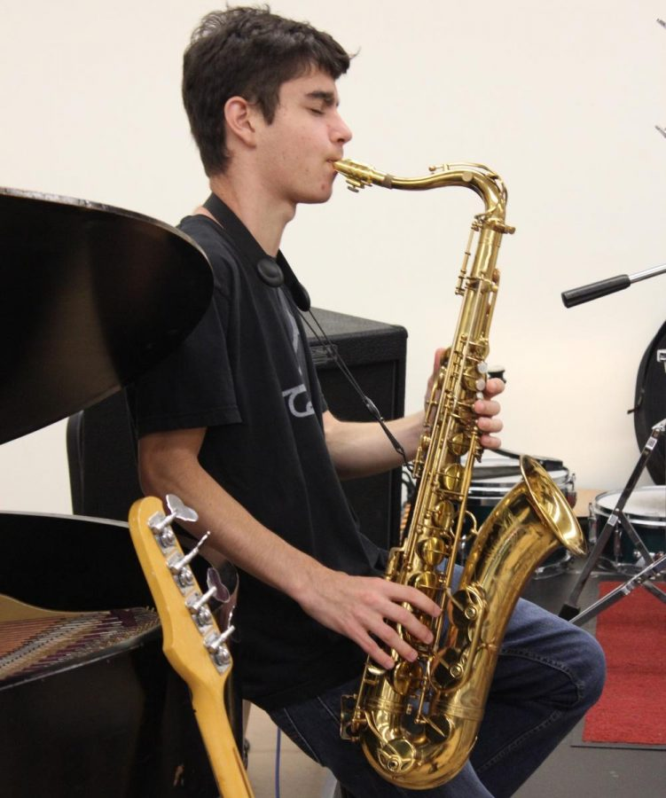 Junior Michael Schwartz plays the saxophone at practice last week.