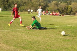 Senior Miguel Rodriguez rolls the ball past the goalie within the first five minutes of the game.