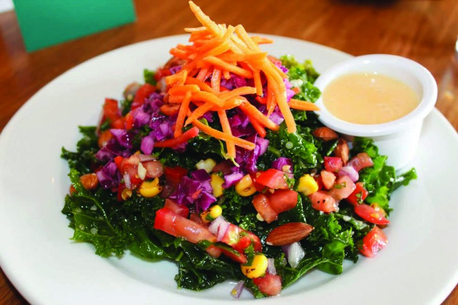 THE ALL-HAIL KALE salad served at Veggie Grill is full of kale, red cabbage, shredded carrots, quinoa,  yellow corn salsa, and almonds with a ginger-papaya vinaigrette.