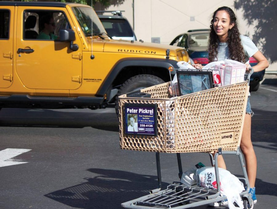 Junior Asha Cummings pushes a shopping cart filled with plastic bags at the Corte Madera Safeway on Tuesday, Oct. 7. Once the ban goes into effect in July 2015, consumers will no  longer be able to buy single-use plastic bags.