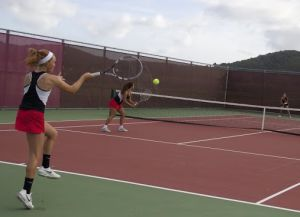 The varsity doubles team returns the long lob back over the net.