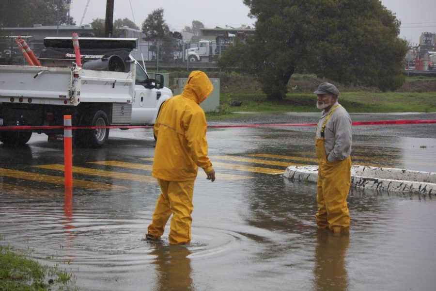 Redwood maintenance workers stand by the entrance to the flooded parking lot.