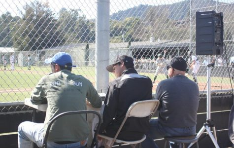 Capers Wolkom (middle) observes a Varsity baseball game