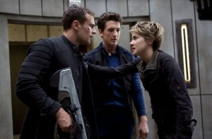 Tris Prior, portrayed by Shailene Woodley, (right) and her boyfriend Tobias Eaton (Theo James, left) debate their attack plan with Peter Hayes (Miles Teller),