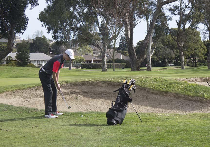 Gearing up for a chip, senior Sander French competes in a match at the Peacock Gap golf course on Thursday, March 12.