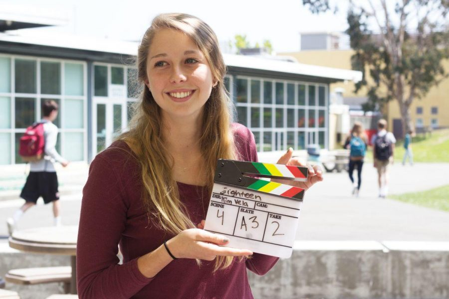 Standing with one of her clapboards from her set junior Kim Vela prepares to direct one of her manny current projects, which include