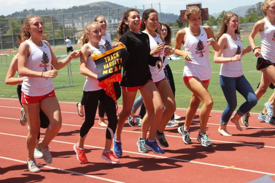 The girl's track team runs around the track with their MCAL pennant.