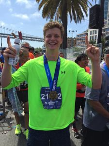 Celebrating his completion of the marathon, senior Cole Schneider smiles for the camera while sporting his new medal.