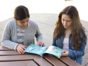 PUBLISHED JUNIOR DUO survey their book, while seated in the quad. After years of hard work their children's picture book,
