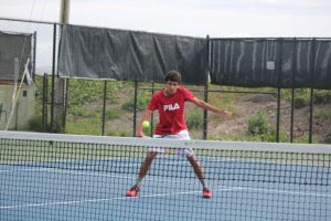 Senior Nic Barretto practices his backhand while playing against his brother Paull