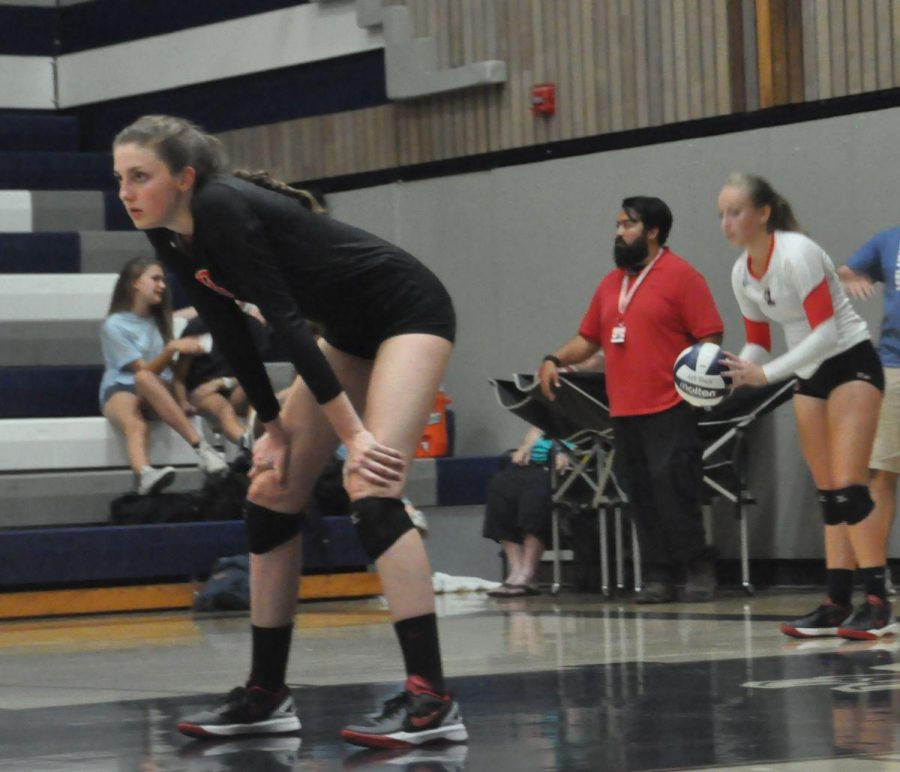 Junior McKenzie Cooke prepares for the next point while senior Lily Barber is about to serve.