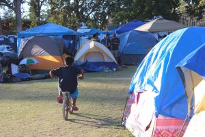 A young boy rides his bike through the maze of tents at the Calistoga evacuation site.