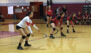 Redwood players prepare to return the incoming serve.