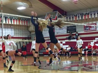 Seniors Elly Lundberg and Marguerite Spaethling jump up to block a San Rafael opponent.