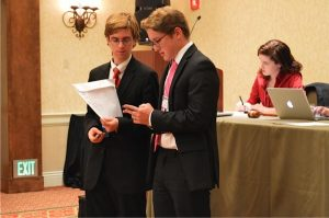 Miles Johnson (on right) consults with another junior statesmen during a debate.