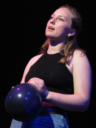 Clenching a black balloon, junior Kate Kiehfuss recites an original slam poem for the upcoming Advanced Drama production In a Nutshell.