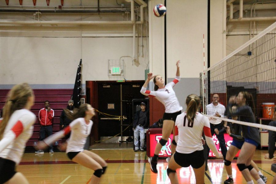 Senior Amanda Lamar approaches and gets ready to hit a ball during the girls' varsity volleyball game today