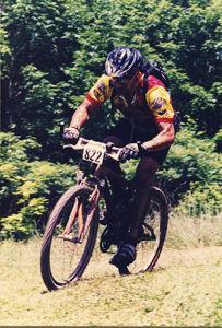 Paul Ippolito bikes on a grassy trail.