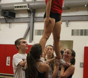 Freshman Max Dostal helps  teammates stunt during practice