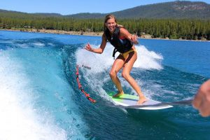 Junior Jacqueline Racich rides on a wake surf board in Tahoe.