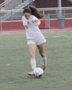 Junior Lily Armstrong dribbles the ball in the rain.