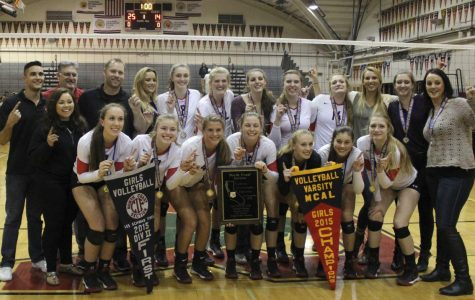 The girls' varsity volleyball team poses with the NCS DII championship banner, the NCS DII plaque, and the MCAL championship banner(From left to right).