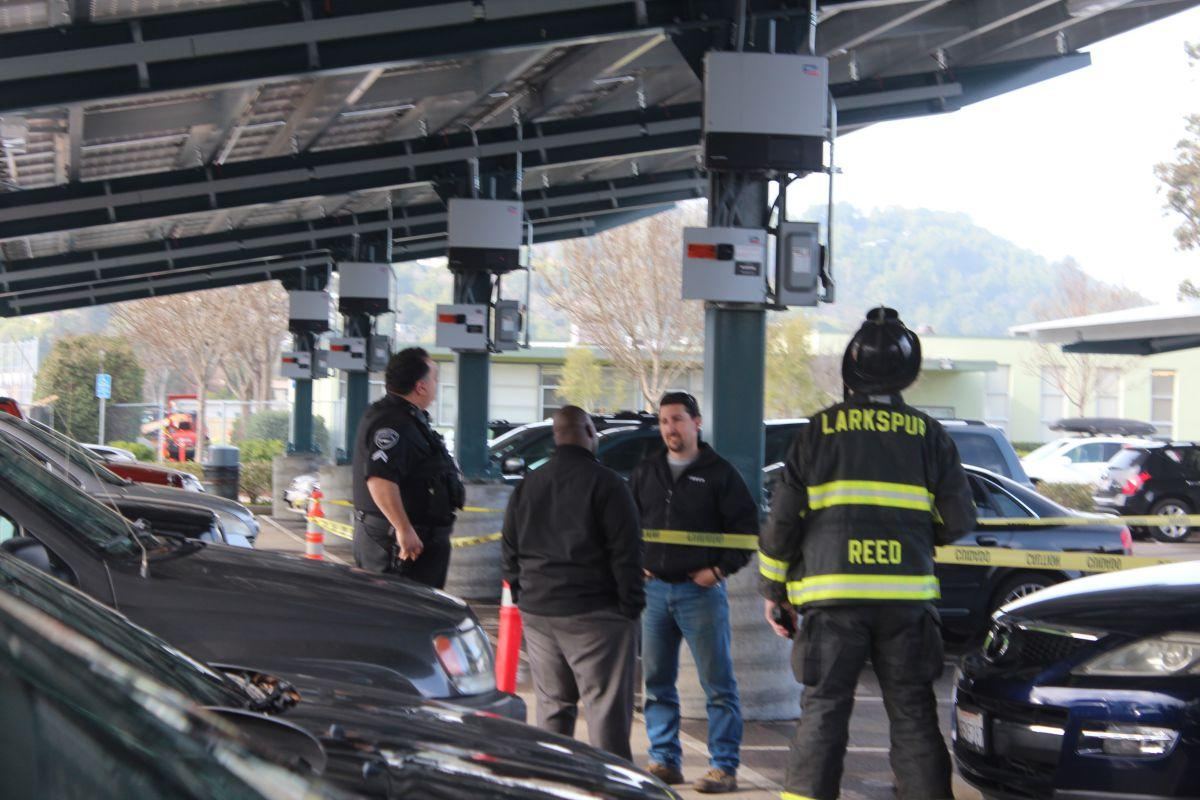 Assistant Principal, Mr. Pratt, a fireman, a police man, and a district official look at the smoking solar panel inverter