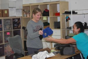 Entrepreneur Sarah Oliver passes a completed handbag to one of her employees. Sarah Oliver handbags are knitted by senior citizens of the Redwoods Retirement Community and customized with either a gold or silver brooch.