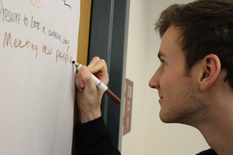 Junior Brendan Shepard writes on the wall during an activity about relationships and their impact on mental health.