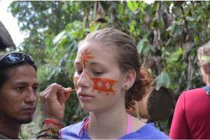 Un guÍa muestra a Hartwell uno de los usos del achiote, para teñir la piel, en el bosque lluvioso de la amazonía a lado del Río Napo.