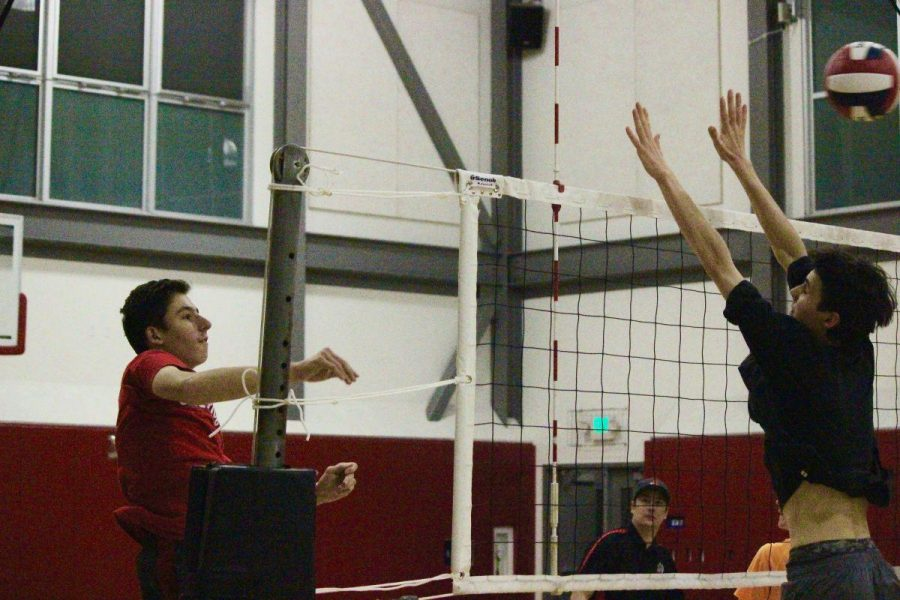Coach Tahan Minakov watches as junior Andrew Lupario hits the ball during a drill.