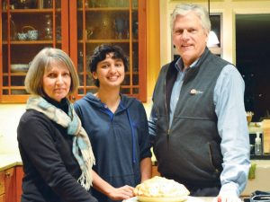 Sophomore Aru Kundhardt smiles  with her parents, Susan and David