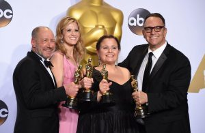 Faust, second from left, celebrates her Academy Award with her co-producers.
