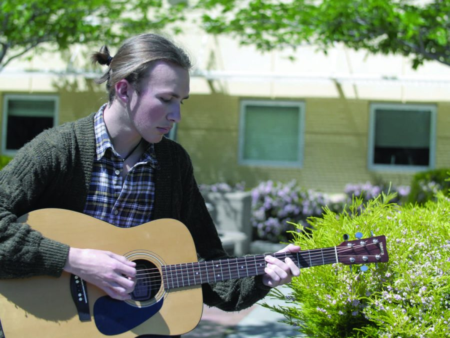 SENIOR JAKE BALDWIN rehearses on his guitar. Baldwin often uses music sharing sites like SoundCloud to share his musical talents.